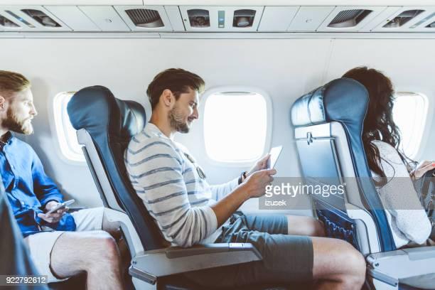 Male passenger using digital tablet during flight