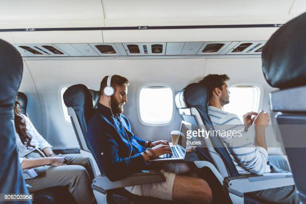 male passenger using laptop during flight - passeggero foto e immagini stock