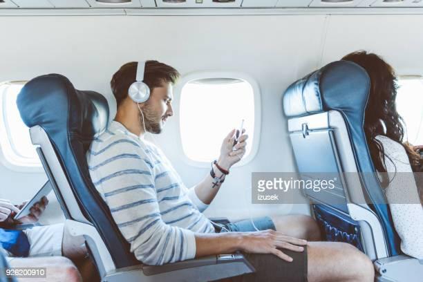 Male passenger using mobile phone during flight