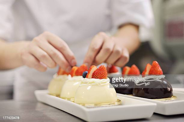 Male pastry chef decorating cake