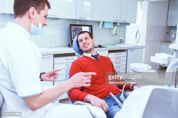 mannelijke patiënt gaat bij de tandarts voor de eerste keer - geval stockfoto's en -beelden