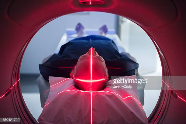 Male patient in medical scanner with red lights