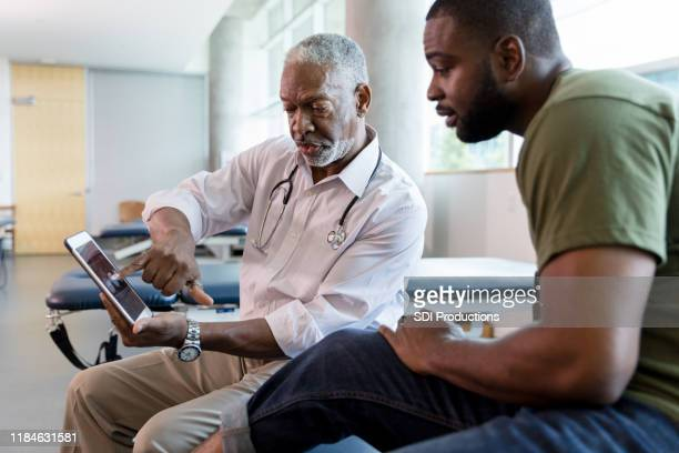 male patient looks with interest at x-rays on digital tablet - medical building stock photos and pictures