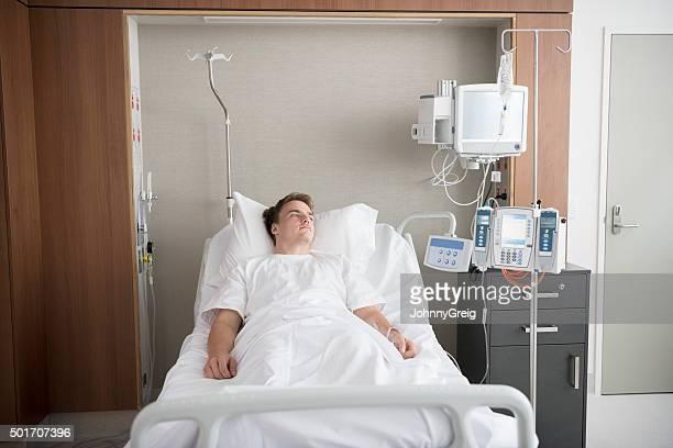 Paciente de sexo masculino de yacer en la cama de hospital ward en recuperación