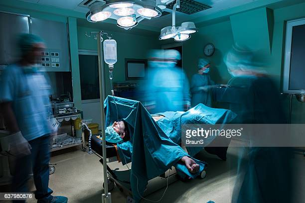 Male patient on operating table among blurred surgeons.
