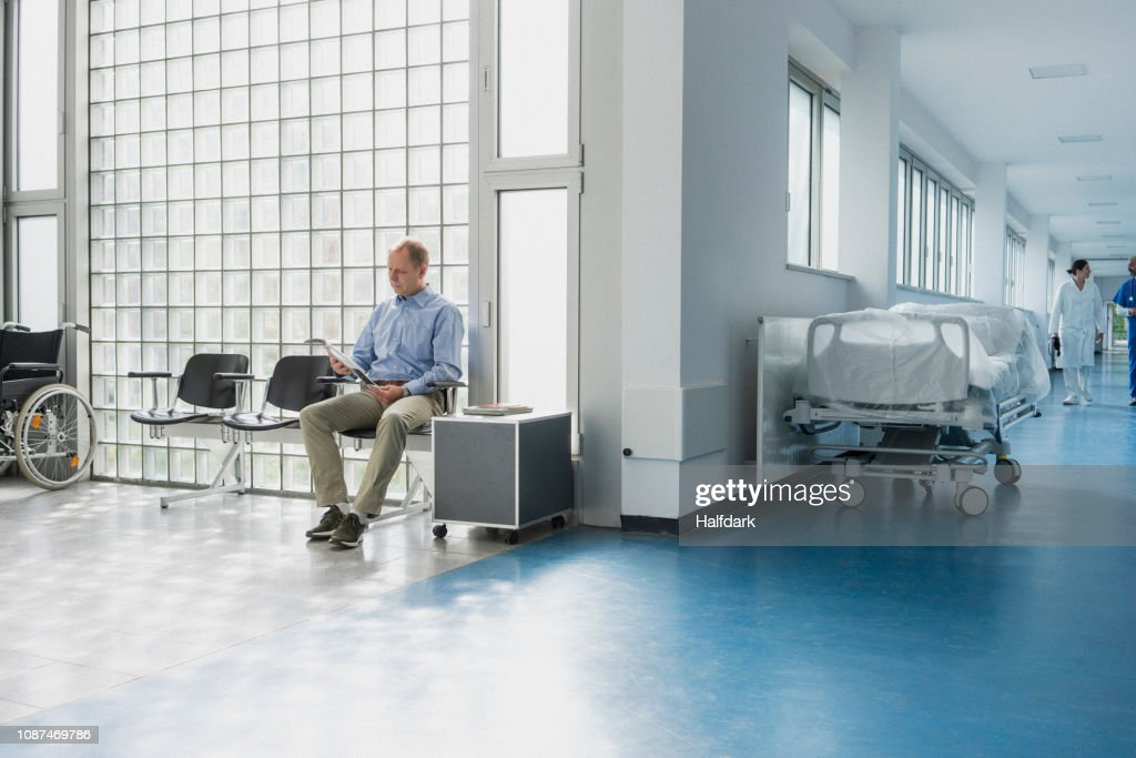 Male patient reading magazine, waiting in hospital waiting room : Stock Photo