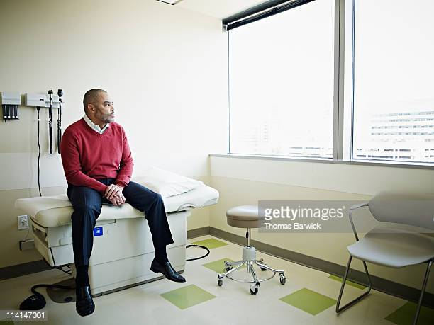 Male patient sitting on exam table in clinic room