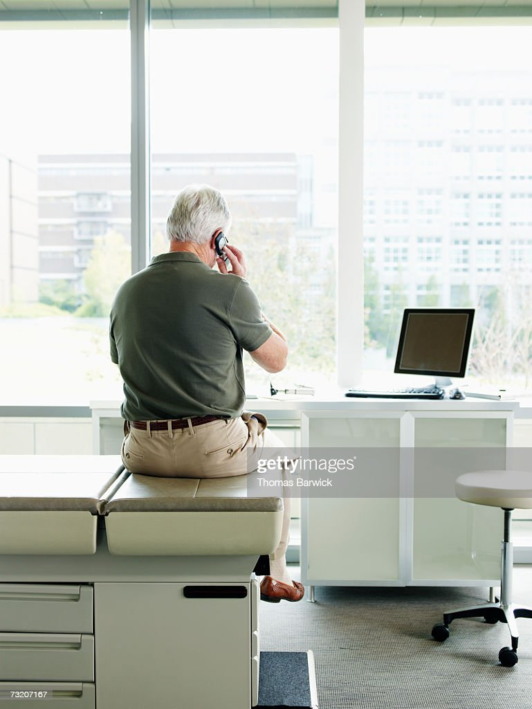 Male patient sitting on exam table in exam room, talking on mobile phone, rear view : Stock Photo