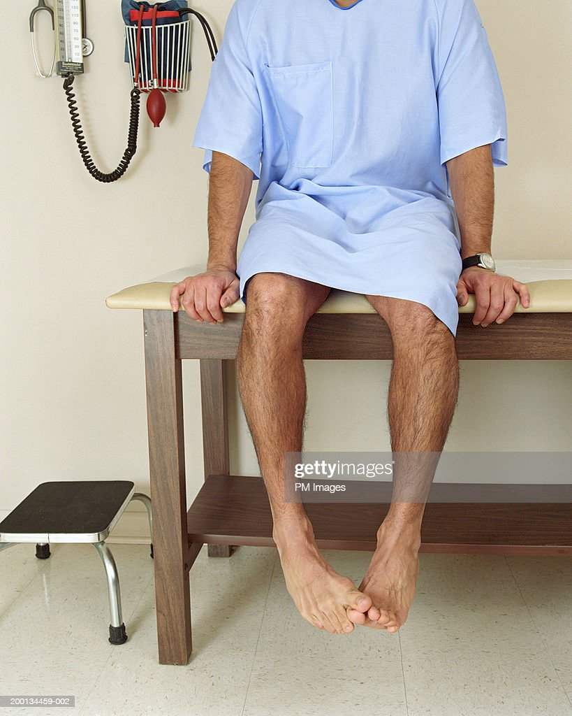 Male patient sitting on examining room table, mid section : Stock Photo