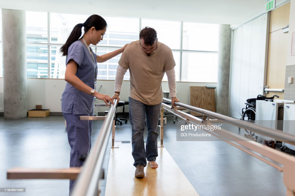 Male patient takes first steps using orthopedic parallel bars : Stock Photo