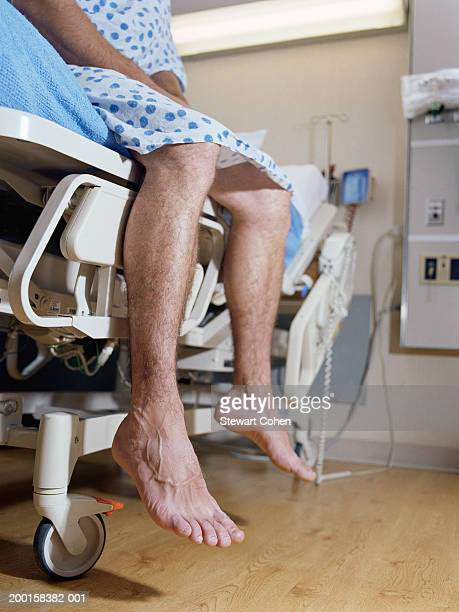 Male patient's legs dangling on side of hospital bed