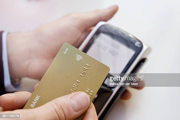 Male pays with creditcard using payment terminal.