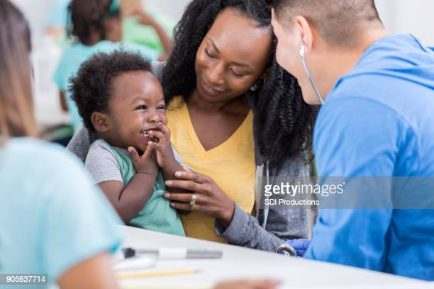 male pediatrician examines baby boy in free clinic - community center stock pictures, royalty-free photos & images