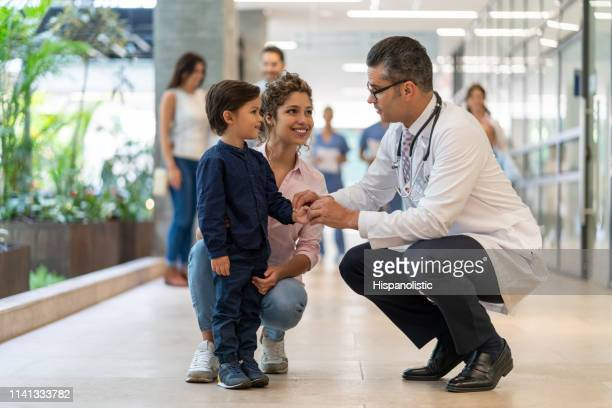 male pediatrician talking to his little patient who is standing next to his mom all smiling - paediatrician stock pictures, royalty-free photos & images