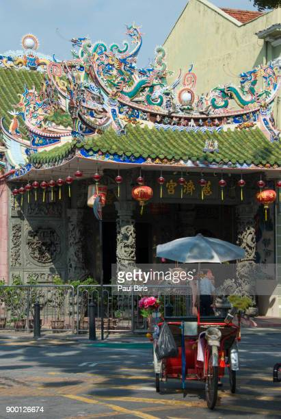 male pedicab riders in front of yap kongsi temple, george town, malaysia - george town penang stock photos and pictures