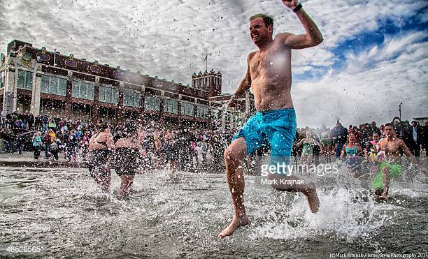 Male person jumps into the frigid Atlantic Ocean during the Sons of Ireland Polar Bear Plunge, New Year's Day 2014, Asbury Park, New Jersey