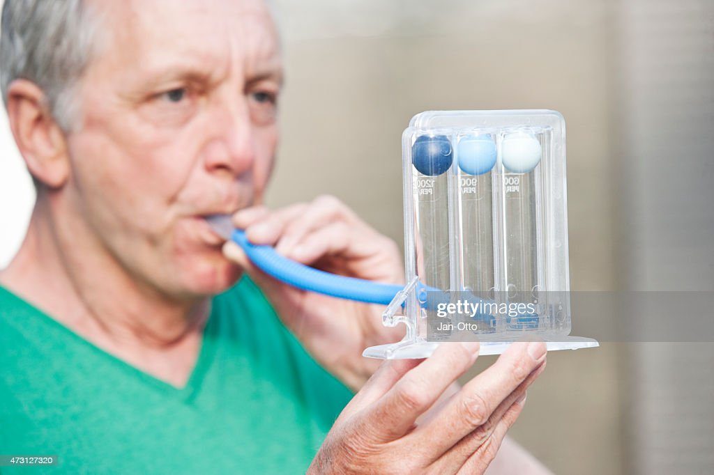 Male person performing lung function test by using a triflow : Stock Photo