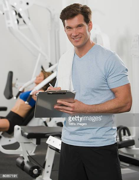 Male personal trainer writing on chart