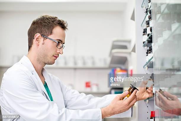 Männlichen Apotheker Medizin-Flasche prüfen