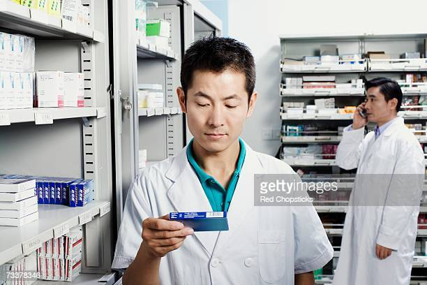 Male pharmacist holding medicine in a store room