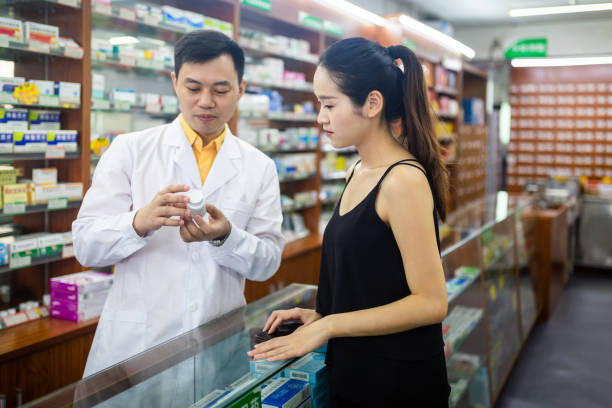 A male pharmacist shows female customers medicines at a pharmacy