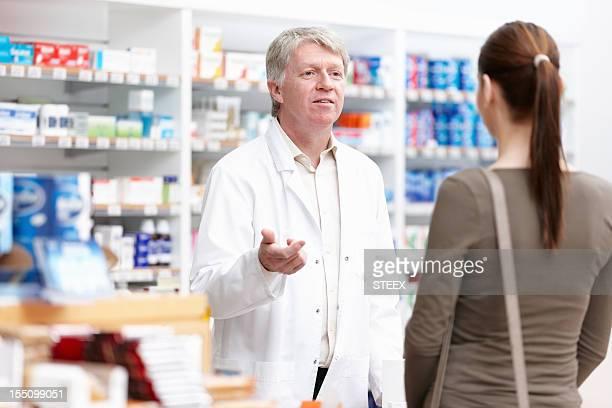 Male pharmacist speaking to customer