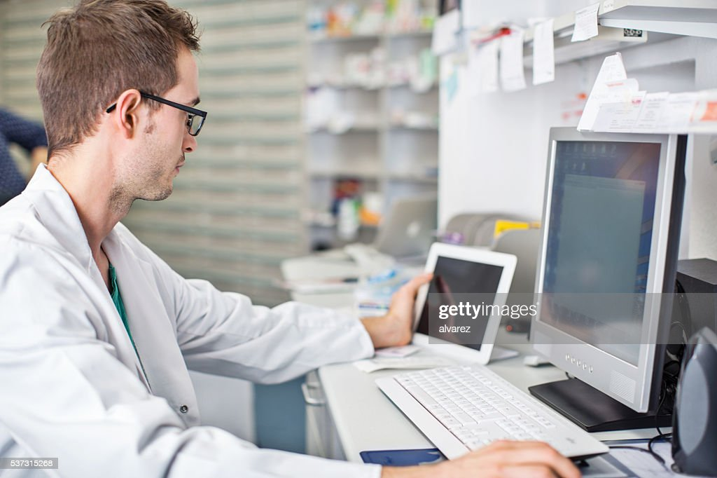 Male pharmacist working at his desk : Stockfoto