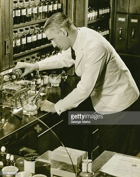 Male pharmacist working in laboratory, (B&W), (Elevated view)