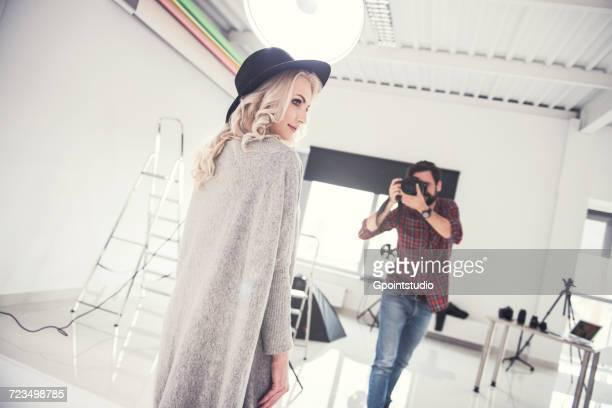 male photographer photographing female model on studio white background - fotosessie stockfoto's en -beelden