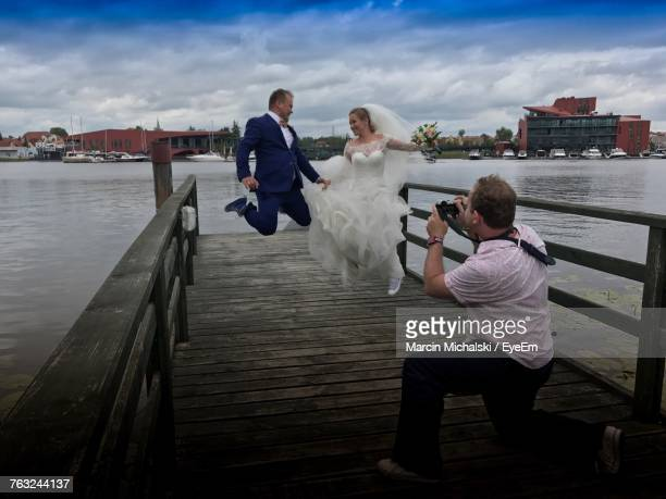 Male Photographer Photographing Wedding Couple Jumping At Pier Over Lake