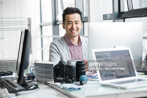 Male photographer working in office with computer