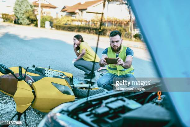 male photographing car damage during traffic accident - motorcycle accident stock pictures, royalty-free photos & images