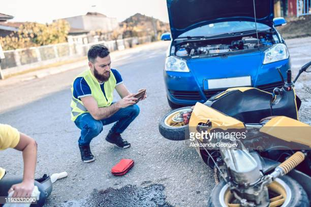 male photographing damage in traffic accident - motorcycle accident stock pictures, royalty-free photos & images