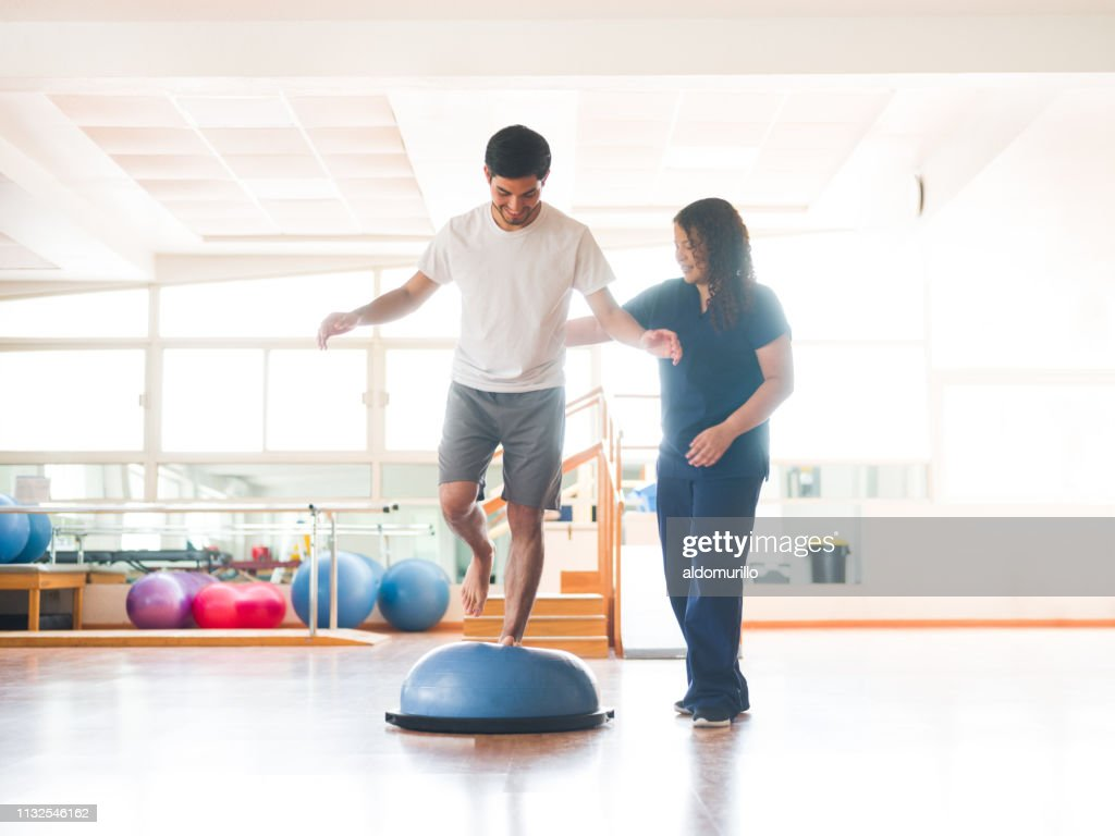 Male physical rehab patient standing on bosu ball : Stock Photo