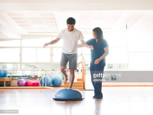 male physical rehab patient standing on bosu ball - sports medicine stock pictures, royalty-free photos & images