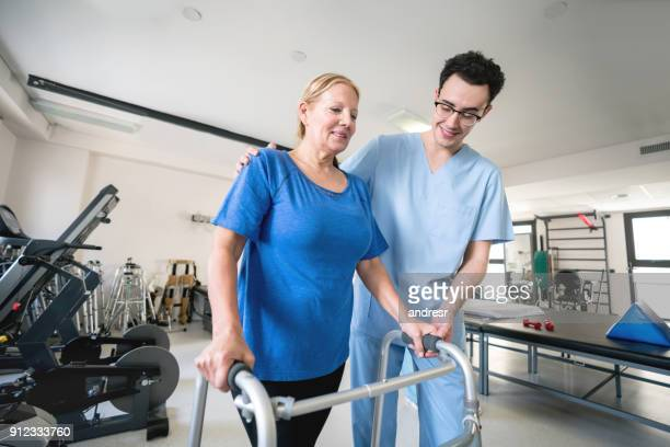 Male physiotherapist helping a senior patient walk using an aid walker