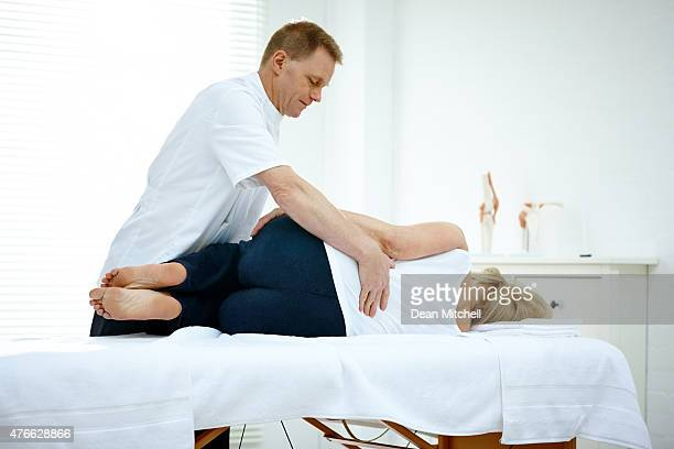 male physiotherapist treating lower back problem of a woman - osteopath stock photos and pictures