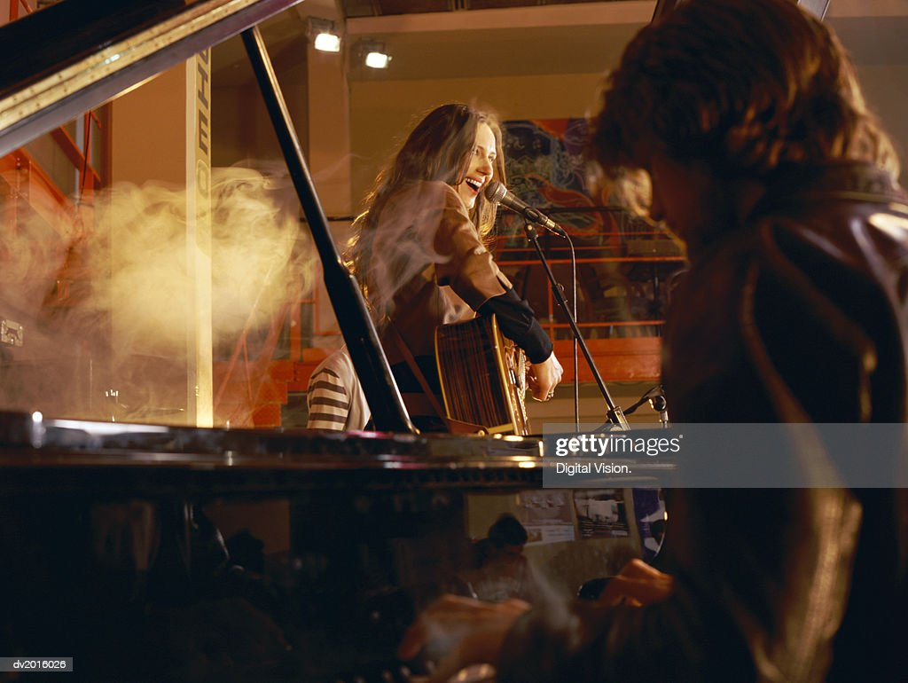 Male Pianist and a Female Guitarist Performing on a Smokey Stage : Stock Photo