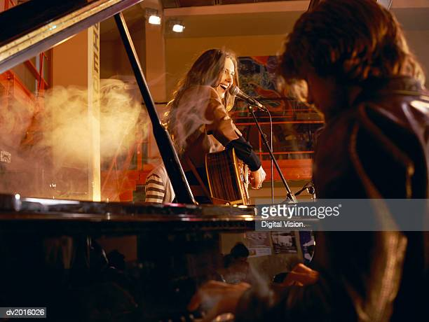 Male Pianist and a Female Guitarist Performing on a Smokey Stage