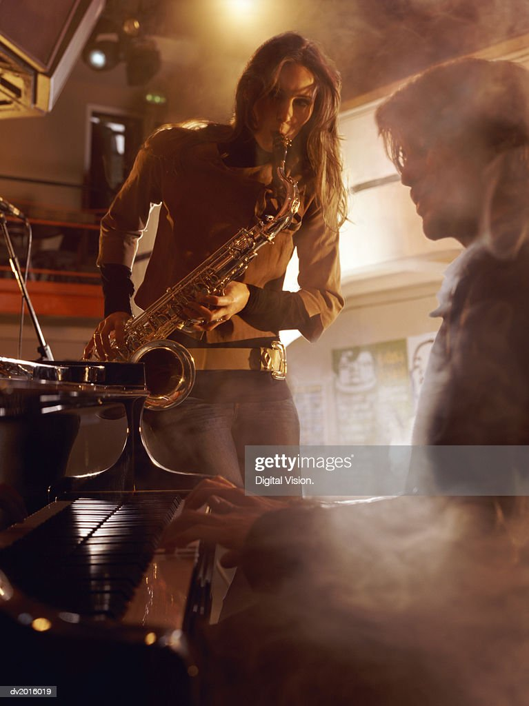 Male Pianist and a Female Saxophonist Playing on a Smokey Stage : Stock Photo