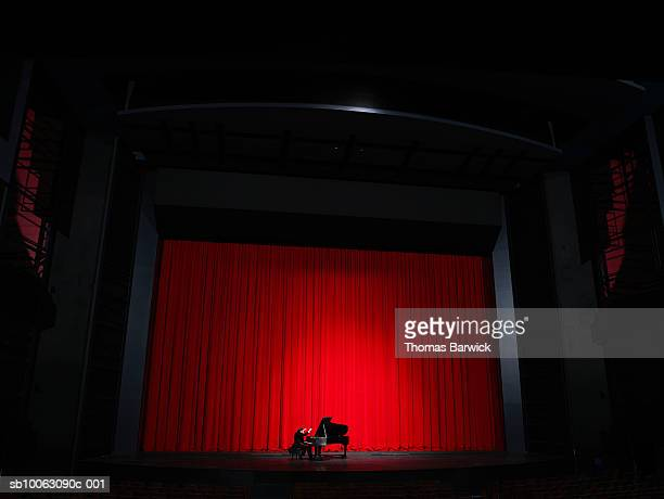 Male pianist performing on grand piano on stage