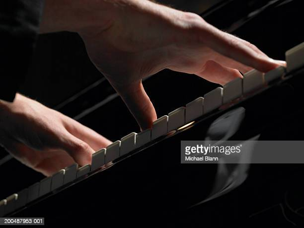 Male pianist playing piano, close-up, low angle view