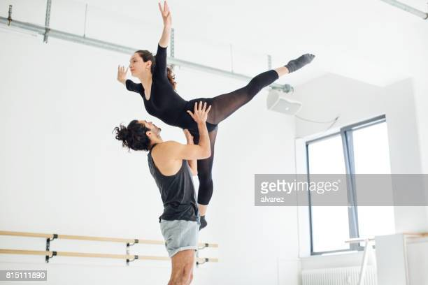 Male picking up female while practicing ballet