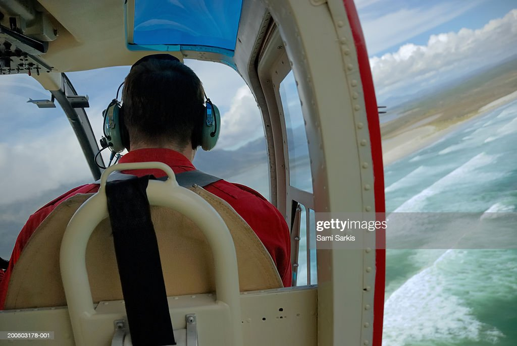 Male pilot wearing headset, flying helicopter, rear view : Stock Photo