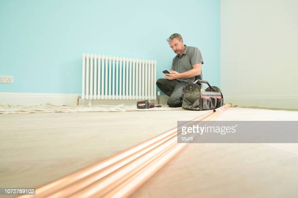 male plumber checking his book keeping - plumbing stock pictures, royalty-free photos & images