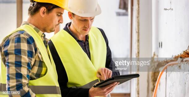 male plumbers with digital tablet - waist up stock pictures, royalty-free photos & images