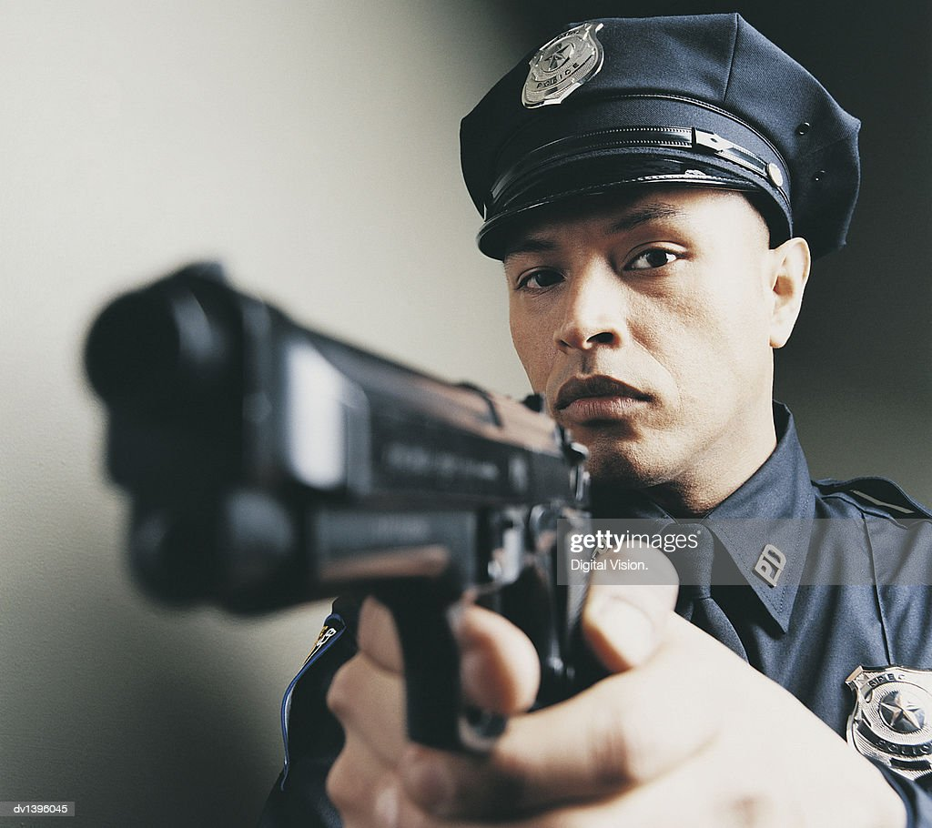 Male Police Officer Holding and Aiming a Gun : Stock Photo