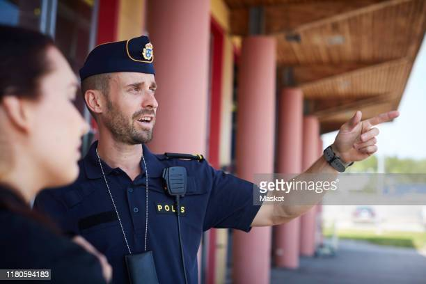 male police officer pointing while directing coworker outside police station - 警察署 ストックフォトと画像