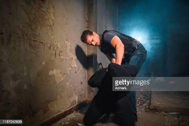 ひざまずく容疑者に手錠をかける男性警察官 - 刑事司法 ストックフォトと画像