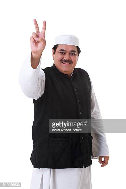 Male politician showing a peace sign over white background